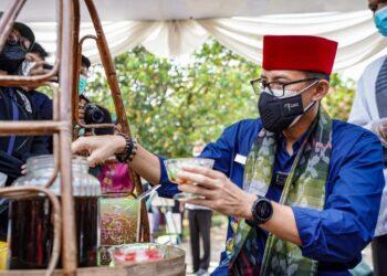 Sandiaga Salahuddin Uno, menikmati minuman segar yang disiapkan masyarakat perkampungan budaya betawi. (Foto : Kemenparekraf)